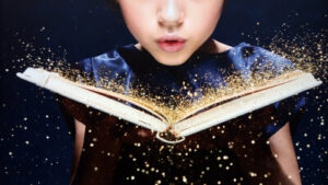 Person blowing sparkles off a book