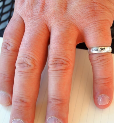 "Photo of a person's hand with ring that says ""fear not"""